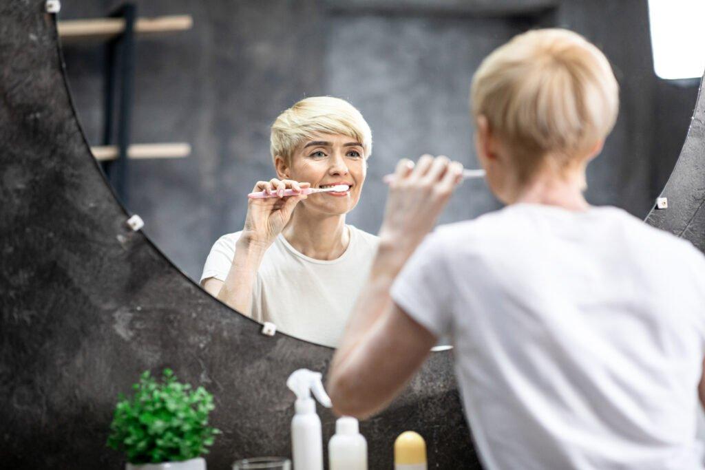 Happy Woman Brushing Teeth In The Morning Standing In Bathroom