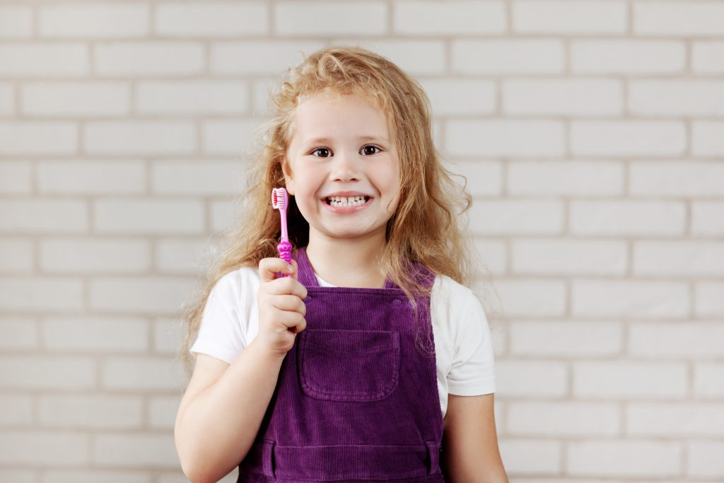 Girl Holding a Toothbrush